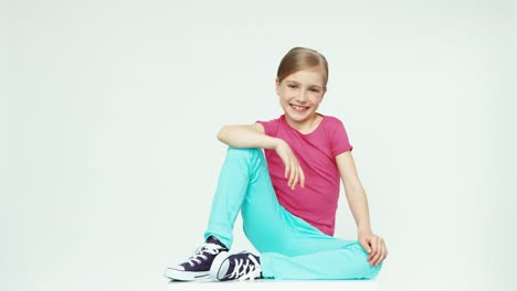 Child-7-8-Years-Sitting-On-The-White-Background-Looking-At-Camera