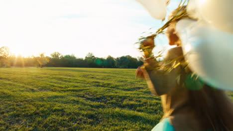 Junges-Mädchen-Rennt-Bei-Sonnenuntergang-Mit-Weißen-Luftballons-über-Das-Feld