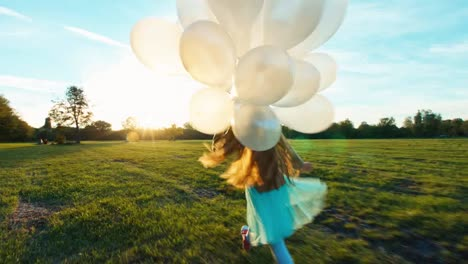 Young-girl-runs-across-field-with-white-balloons-during-sunset-1