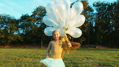 Niño-8-9-Years-Old-Running-At-Camera-And-Holds-Her-White-Balloons-And-Smiling