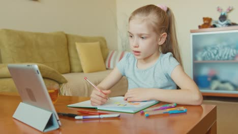 Child-Drawing-In-A-Notebook-And-Looking-At-Tablet-PC