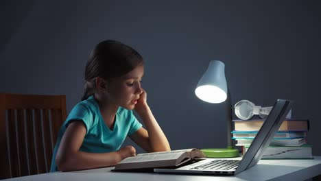 Child-Girl-7-8-Years-Old-Reading-Textbook-In-Her-Desk-In-The-Night