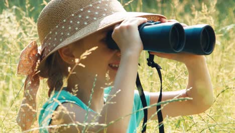 Laughing-young-nature-lover-looking-through-binoculars-in-the-high-grass-2