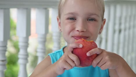 Portrait-Of-A-Little-Girl-Which-Eating-A-Big-Red-Peach-And-Looking-At-The-Camera