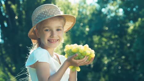 Portrait-Of-Farmer-Girl-Sniffing-And-Holding-A-Bunch-Of-Grapes-And-Smiling