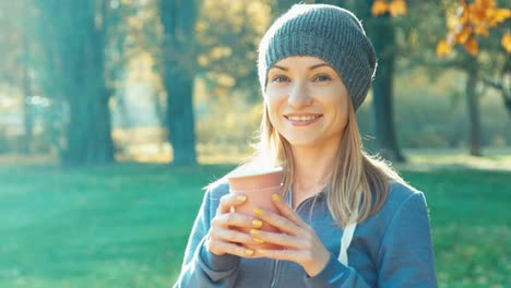 Portrait-Smiling-Young-Woman-Holding-Cup-Of-Tea-And-Drinking-Tea-Outdoors-And