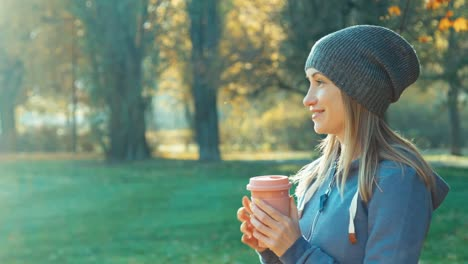 Portrait-Young-Adult-Woman-Holding-Cup-Of-Tea-Outdoors-And-Looking-At-Camera