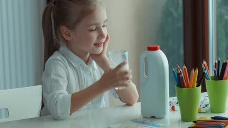 Preschooler-Girl-Drinking-Milk-Looking-At-Window-And-Camera-And-Smiling-02