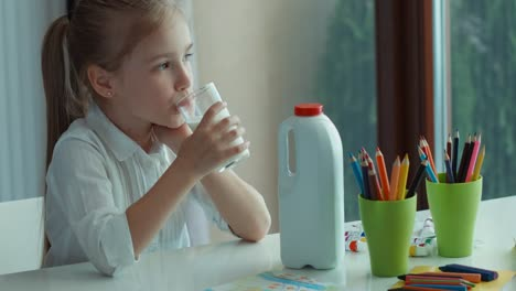 Preschooler-Girl-Drinking-Milk-Looking-At-Window-And-Camera-And-Smiling-01
