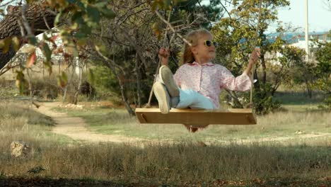 Preschooler-Girl-In-Sunglasses-On-The-Swing-Have-Fun