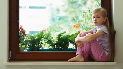 Sad-Girl-Sitting-On-A-Windowsill-And-Looking-Out-The-Window