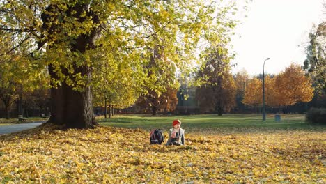 Schooler-Girl-7-Years-Old-Holding-Cup-Of-Tea-And-Sitting-On-The-Autumn-Leaves