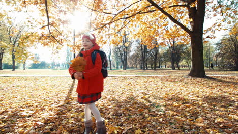Schoolgirl-Child-Spinning-With-Bouquet-Of-Leafs-In-The-Park-In-The-Autumn