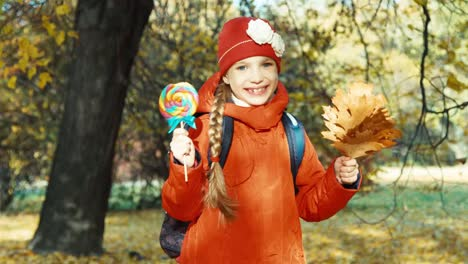 Schoolgirl-Holding-Sweets-And-Bouquet-Of-Leafs-In-The-Park-In-The-Autumn