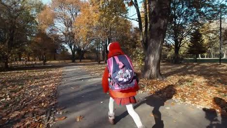 Colegiala-Corriendo-En-La-Escuela-En-El-Parque-En-Otoño