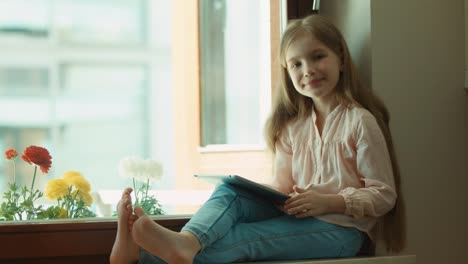 -Blond-little-girl-using-tablet-and-sitting-on-a-window-sill