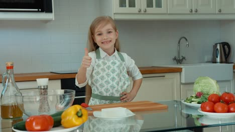 Niña-Sonriente-Chef-En-La-Cocina-Mirando-A-La-Cámara-Pulgar-Arriba-Ok