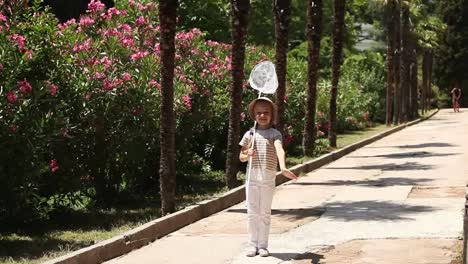 Smiling-Girl-With-A-Butterfly-Net-Looking-At-The-Camera-And-Waving-Hand