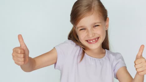 Thumbs-Up-Ok-Girl-Is-On-The-White-Background-Laughing-Child-Closeup