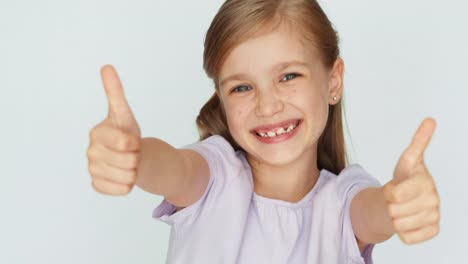 Thumbs-Up-Ok-Girl-Laughing-At-Camera-Child-Is-On-The-White-Background-02