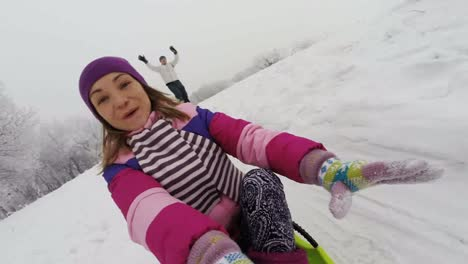 Woman-Riding-Down-A-Snowy-Hill-On-A-Sledge