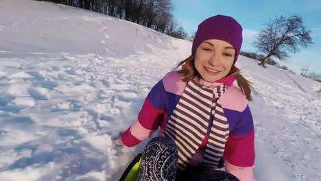 Woman-Riding-Down-A-Steep-Hill-On-A-Sledge-Boyfriend-Waving-Hand