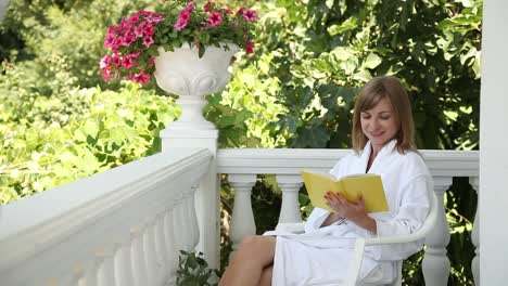 Young-Adult-Reading-A-Book-And-Smiling-At-Camera-She-Is-Dressed-In-A-Bathrobe