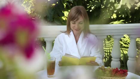 Young-Adult-Reading-A-Book-And-Smiling-At-The-Camera-Girl-Sitting-At-A-Table