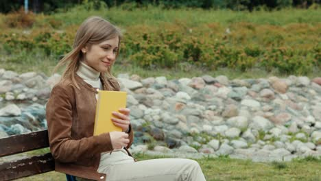 Young-Adult-Woman-Hugging-A-Book-Girl-Sitting-On-A-Bench-In-The-Park
