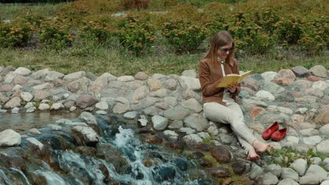 Young-Adult-Woman-Resting-In-The-Park-And-Reading-A-Book-Girl-Is-Sitting
