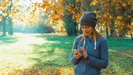 Young-Adult-Woman-Smiling-At-Camera-And-Using-Smartphone-In-The-Park-In-The-A