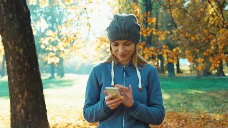 Young-Adult-Woman-Using-Smartphone-And-Walking-At-Camera-In-The-Park-In-The-A