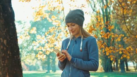Junge-Erwachsene-Frau-Mit-Smartphone-Im-Park-Im-Herbst