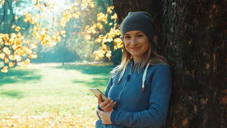 Young-Adult-Woman-Using-Smartphone-Smiling-At-Camera-Standing-Near-Tree-In-Th