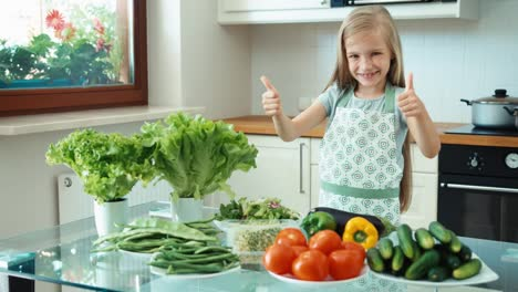 Young-Chef-With-Vegetables-Near-Kitchen-Table-And-Smiling-At-Camera