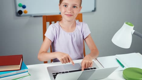 Child-Girl-7-8-Years-Using-Laptop-In-Her-Desk-And-Smiling-At-Camera-Thumb-Up