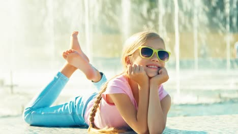 Child-Lying-On-Fountain-Background-At-Sunny-Day-And-Waving-Hand