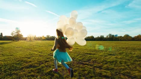 Child-Running-Across-The-Field-At-Sun-In-Sunset-And-Holds-Her-Balloons
