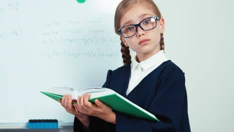 Close-Up-Hands-Little-Student-Girl-Holding-Book-Near-Whiteboard