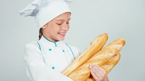 Close-Up-Portrait-Baker-Girl-Child-Holds-Bread-Baguettes-And-Smiling-At-Camera