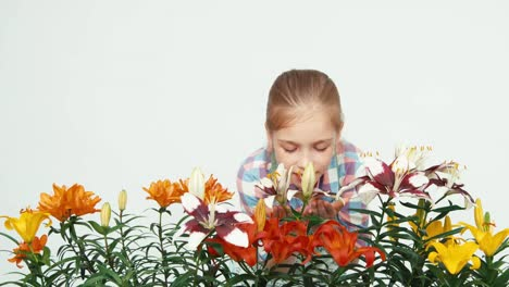 Close-Up-Portrait-Flowergirl-Sniffing-Flower-And-Smiling-At-Camera-On-White