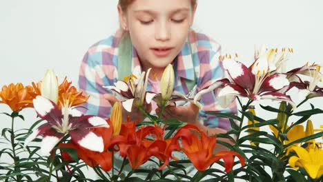 Close-Up-Portrait-Flowergirl-Sniffing-Flowers-And-Smiling-At-Camera-On-White