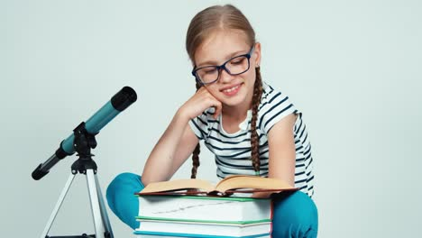 Close-Up-Portrait-Girl-7-8-Years-Old-Reading-Book-Near-Telescope