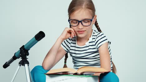 Close-Up-Portrait-Girl-7-8-Years-Old-Reading-Book-Near-Telescope-Panning