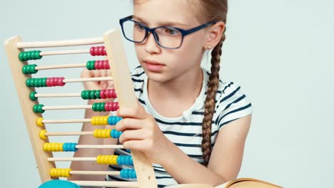 Close-up-girl-using-abacus-and-sitting-near-a-stack-of-books