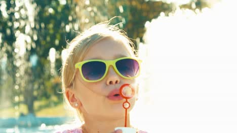 Close-Up-Portrait-Girl-Blowing-Soap-Bubbles-Near-Fountain-And-Laughing