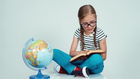 Close-Up-Portrait-Girl-Reading-Book-And-Looking-At-Camera-On-White-Near-Globe