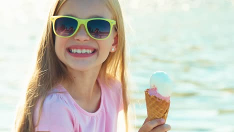 Close-Up-Portrait-Happy-Child-Girl-Eating-Ice-Cream-Sitting-Near-Fountain