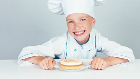 Close-Up-Portrait-Happy-Little-Chef-Cook-Looking-At-Small-Cake-With-And-Smiling