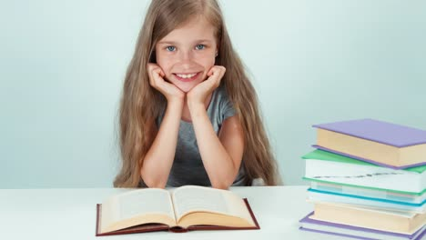 Close-Up-Portrait-Happy-Schoolgirl-7-8-Years-Old-Reading-Book-On-The-Table